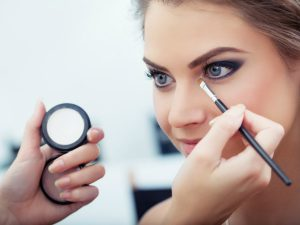 Make-up artist applying white eyeshadow in the corner of model's eye and holding a case with eyeshadow on background close up