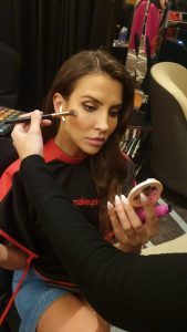 Student doing makeup on the model for the Determined Fashion Show